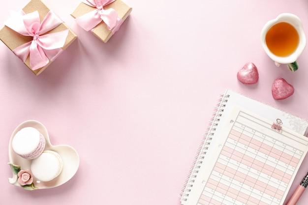 Geschenkdoos of geschenkdoos en bloemen op roze tafelblad weergave. Premium Foto