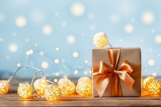 Geschenkdoos omwikkeld met knutselpapier en lint met guirlande lichten Premium Foto