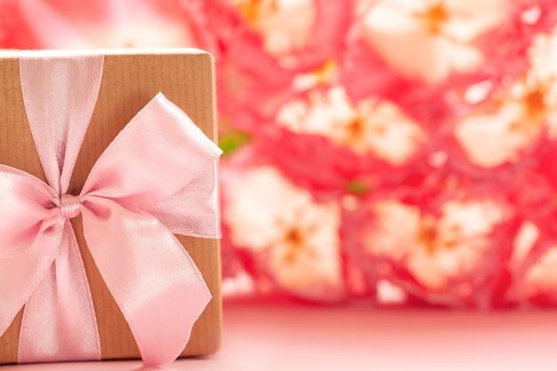 Geschenkdoos omwikkeld met kraftpapier en roze strik op roze bloemen achtergrond. Premium Foto