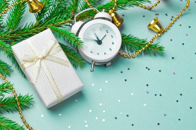 Geschenkdoos op een vuren tak en een witte wekker Premium Foto