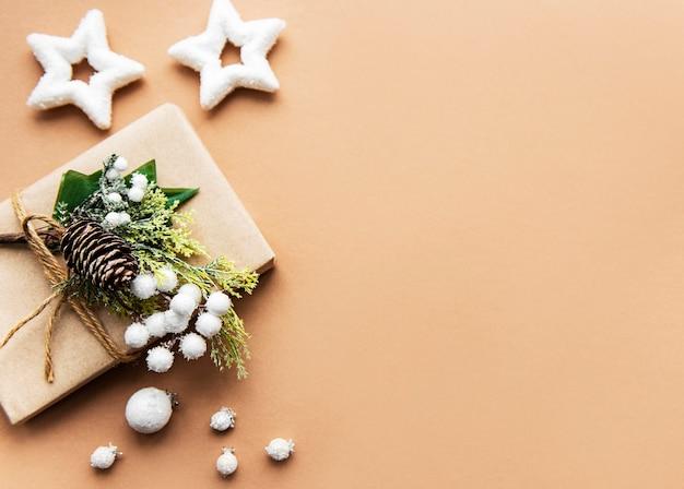 Geschenkdoos verpakt in kraftpapier op een bruine achtergrond Premium Foto