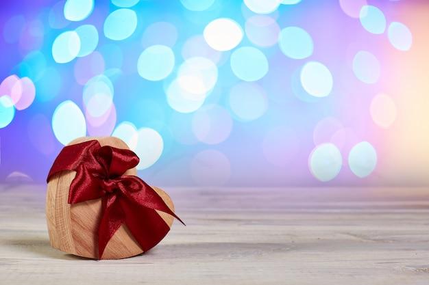 Geschenkdoos voor ringen. houten kist hart met lint strik op onscherpe achtergrond. wenskaart Premium Foto