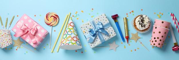 Geschenkdozen en verjaardag accessoires op blauwe achtergrond, bovenaanzicht Premium Foto