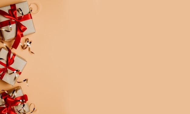 Geschenkdozen gebonden met rode linten en confetti op pastel tafel met kopie ruimte voor tekst. bovenaanzicht, plat leggen. Premium Foto