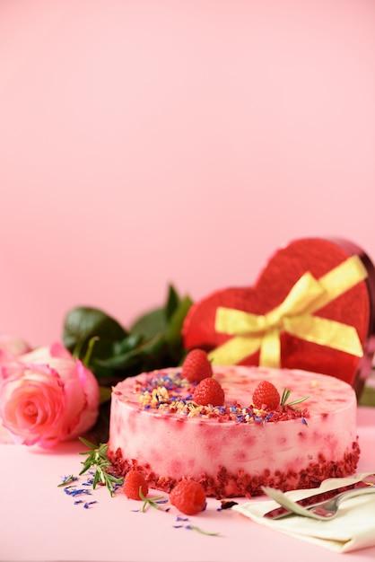 Geschenkdozen in de vorm van harten, rozen, frambozencake met verse bessen, rozemarijn en droge bloemen. valentijnsdag concept. presenteer met liefde Premium Foto
