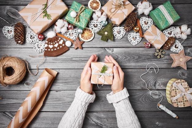 Geschenkdozen, kerstversiering en dennenappels op grijze houten tafel Premium Foto