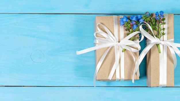 Geschenkdozen met bloemen op een blauwe achtergrond. Premium Foto