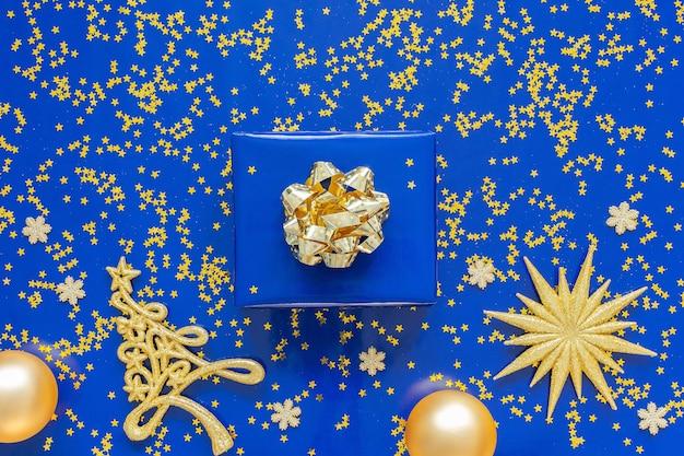 Geschenkdozen met een gouden boog en dennenboom met kerstballen op een blauwe achtergrond, gouden glimmende glitter sterren op een blauwe achtergrond, kerstmis concept, plat lag, bovenaanzicht Premium Foto