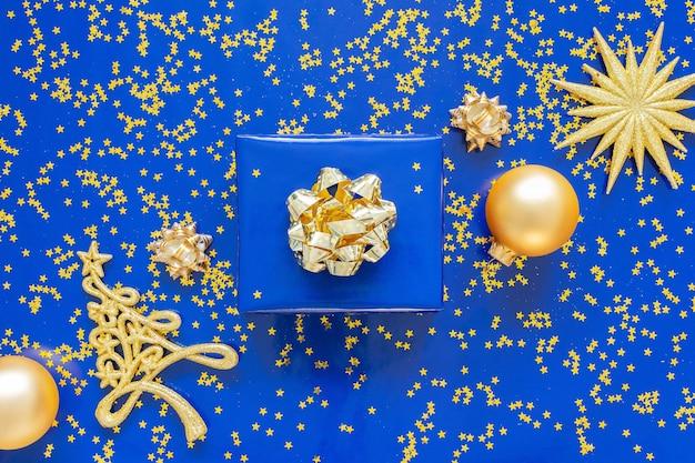 Geschenkdozen met een gouden boog en dennenboom met kerstballen op een blauwe achtergrond, gouden glimmende glitter sterren op een blauwe achtergrond Premium Foto