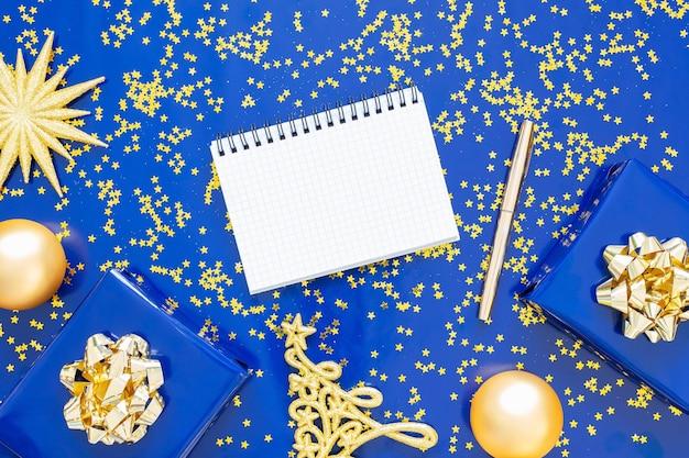 Geschenkdozen met een gouden boog en dennenboom met kerstballen op een blauwe achtergrond, gouden glimmende glitter sterren, open spiraal kladblok en pen, plat leggen, bovenaanzicht Premium Foto