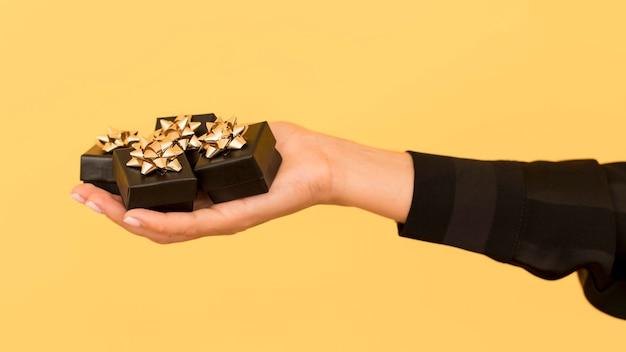 Geschenkdozen met gouden lint voor zwarte vrijdag in de hand gehouden Gratis Foto