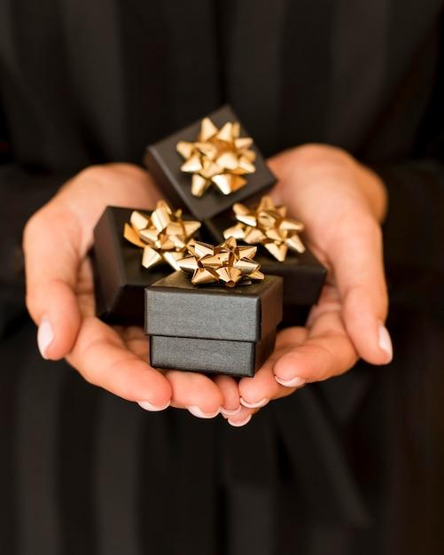 Geschenkdozen met gouden lint voor zwarte vrijdag vooraanzicht Gratis Foto