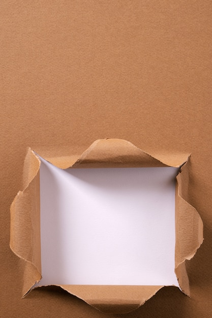 Gescheurd pakpapier vierkant gat achtergrondkaderverticaal Premium Foto