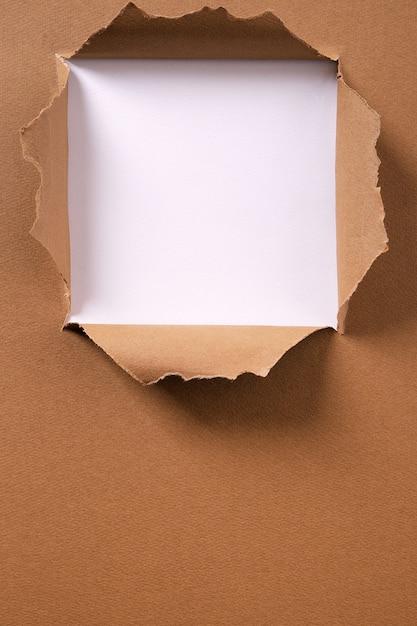 Gescheurd pakpapier vierkant gat verticaal kader als achtergrond Premium Foto
