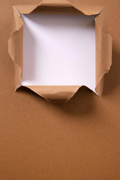 Gescheurd van het pakpapier vierkant gat verticaal kader als achtergrond Gratis Foto