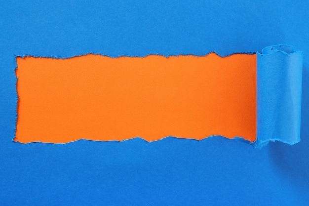 Gescheurde blauw papier middenstrook oranje achtergrond Premium Foto