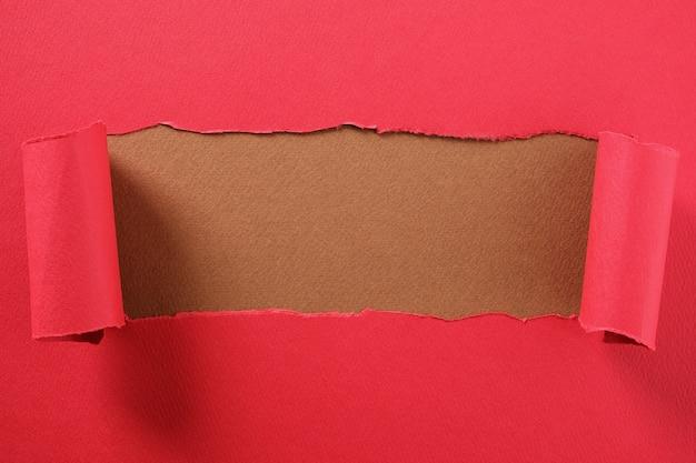 Gescheurde rode papieren strook gekrulde rand onthullend middelste bruine achtergrondgeluid Premium Foto