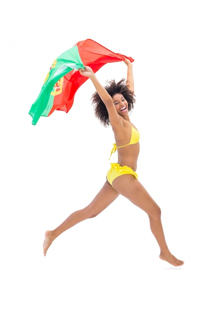 Geschikt meisje in de gele vlag die van portugal portugese vlag houden die lacht Premium Foto