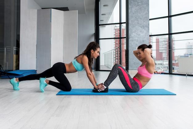 Geschikt sportief meisje die abs training op de vloer in gymnastiek doen met hulp van haar vrouwelijke vriend Premium Foto