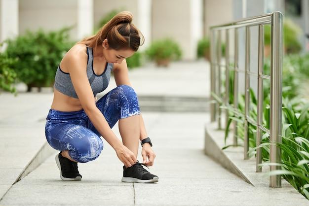 Geschikte aziatische vrouw in sportkleding die schoenveters in straat binden Gratis Foto