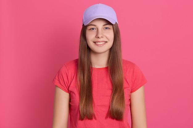Geschikte jonge vrouw die toevallige t-shirt status dragen geïsoleerd over rooskleurige muur. prachtig model in baseball cap Gratis Foto