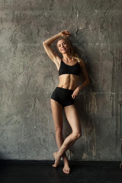 Geschiktheids blondie vrouw die zich dichtbij de muur bevindt Premium Foto