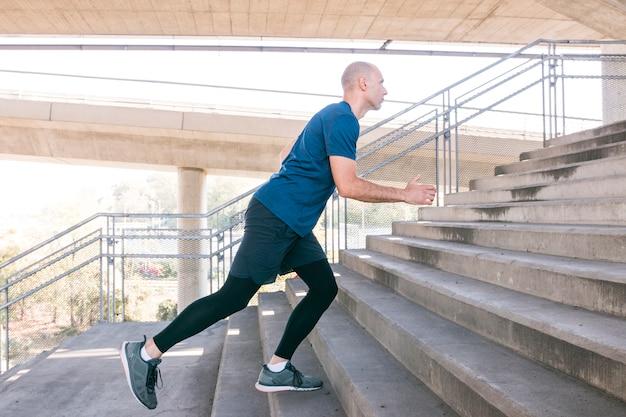 Geschiktheids mannelijke atleet die op concrete trap lopen Gratis Foto