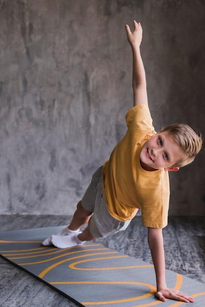 Geschiktheidsjongen die op oefeningsmat uitoefenen voor concrete muur Gratis Foto