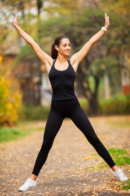 Geschiktheidsmeisje, jonge vrouw die oefeningen in het park doen. Premium Foto