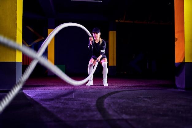 Geschiktheidsvrouw die opleidingskabels voor oefening gebruiken bij gymnastiek. atleet die met strijdtouwen bij dwarsgymnastiek uitwerkt Premium Foto