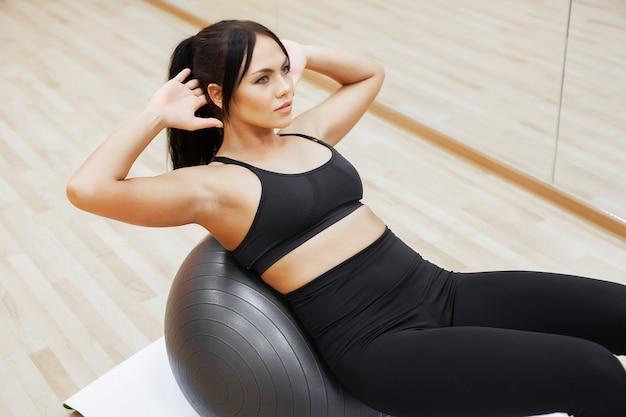Geschiktheidsvrouw, jonge aantrekkelijke vrouw die oefeningen doen die bal gebruiken Premium Foto