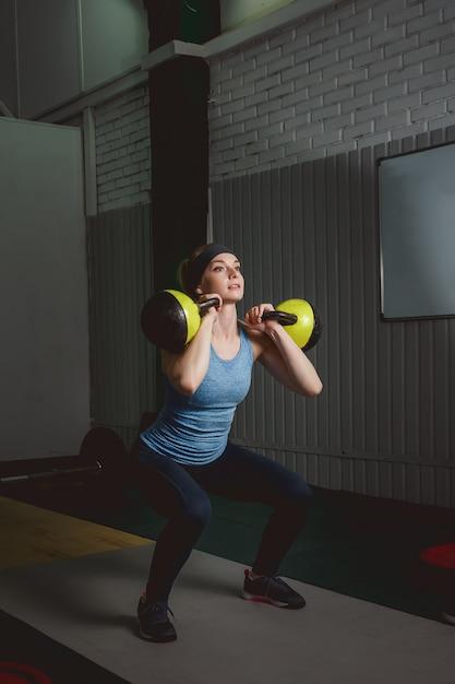 Geschiktheidsvrouw opleiding door kettlebell. fit jonge dame crossfit oefening doen. Premium Foto