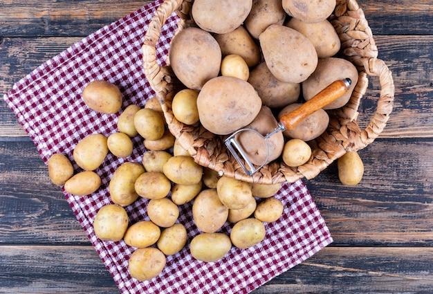 Geschilde aardappelen met aardappelschiller in een mand en op picknick doek, op grijze houten tafel Gratis Foto