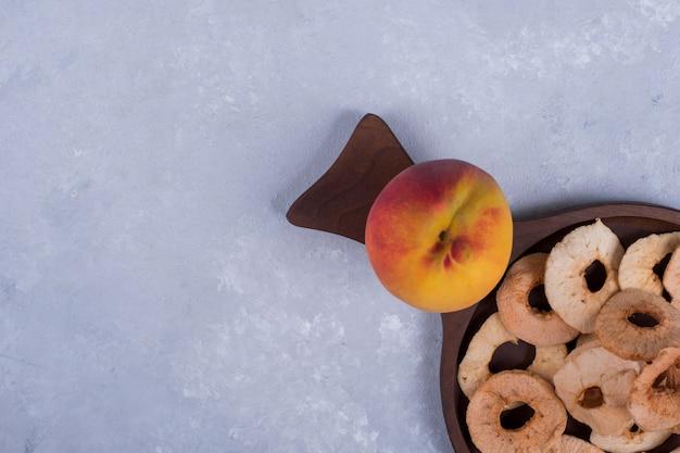 Geschilde, gesneden en droge appels met een perzik op een houten schaal in de hoek Gratis Foto