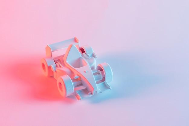 Geschilderde miniatuurformule één auto tegen roze achtergrond Gratis Foto