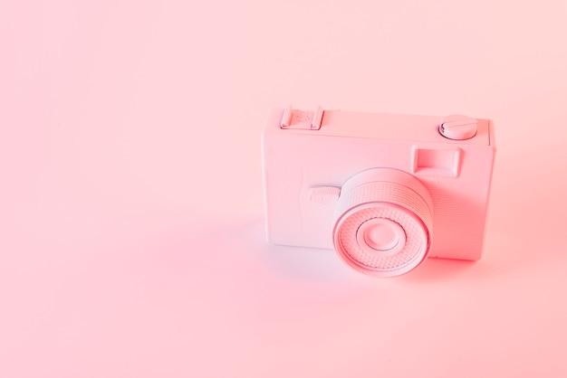 Geschilderde roze camera tegen roze achtergrond Gratis Foto