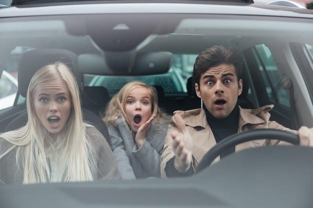 Geschokt bang jonge man zit in de auto met familie Gratis Foto