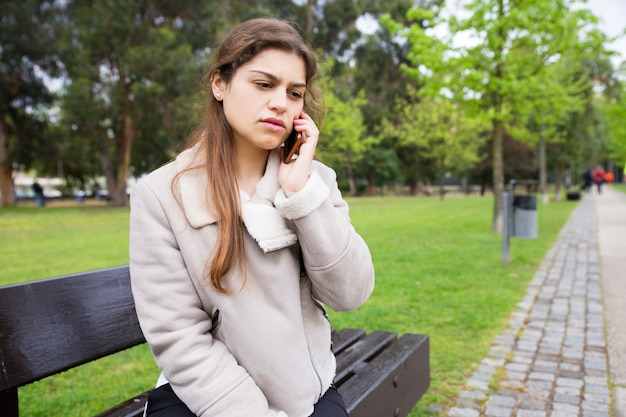 Geschokt boos studentenmeisje die op telefoon spreken Gratis Foto
