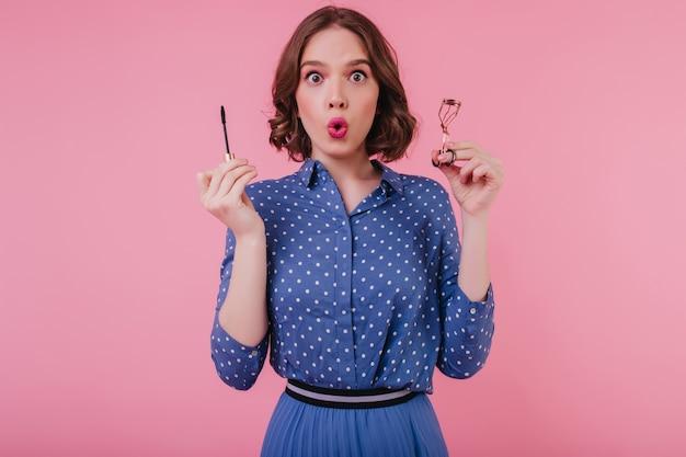 Geschokt donkerogig meisje in trendy blouse poseren op roze muur met mascara. indoor foto van brunette verrast jonge vrouw doet haar wimpers. Gratis Foto
