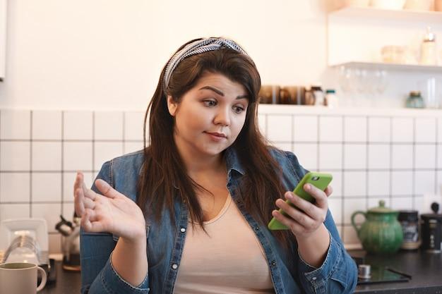 Geschokt emotionele jonge vrouw met overgewicht dragen xxl jeans jasje lezen van een sms in de keuken thuis verbaasd kijken tijdens het surfen op internet met behulp van de mobiele telefoon in de keuken tijdens het ontbijt Gratis Foto