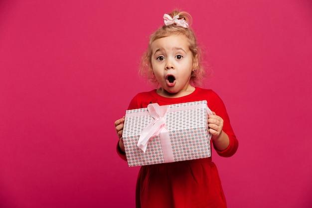 Geschokt jong blondemeisje in de giftdoos van de rode kledingsholding Gratis Foto