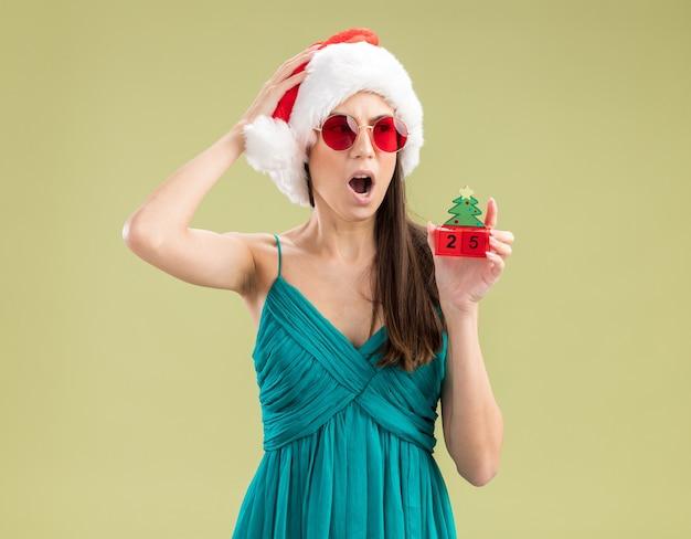 Geschokt jong kaukasisch meisje in zonnebril met kerstmuts legt hand op het hoofd en houdt kerstboom ornament kant kijken Gratis Foto