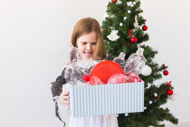 Geschokt kind meisje kijkt met geopende ogen en bezorgde uitdrukking met doos met afval Premium Foto