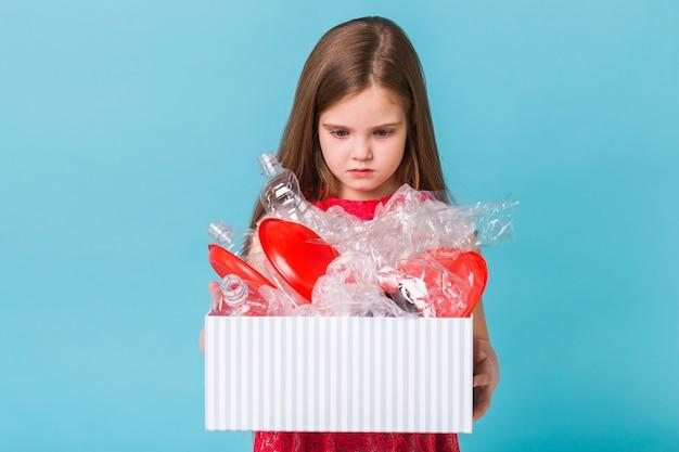 Geschokt klein kind meisje kijkt met geopende ogen met doos met afval Premium Foto
