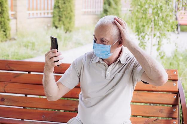 Geschokt man met medische gezichtsmasker met behulp van de telefoon om te zoeken naar nieuws Premium Foto