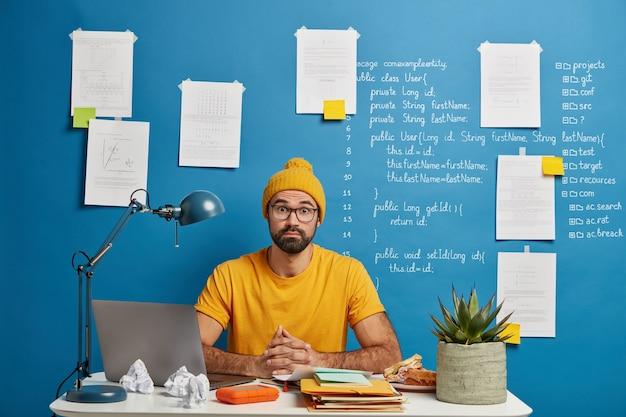 Geschokt mannelijke student vormt op de desktop thuis of op kantoor, gebruikt laptop voor het zoeken naar online onderwijscursussen, bladert door de website voor afstandsonderwijs Gratis Foto