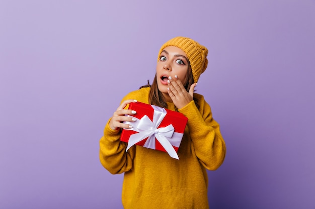 Geschokt meisje in casual trui en hoed poseren met cadeau. binnenportret van debonaire dame met een nieuw jaar dat verbazing uitdrukt. Gratis Foto