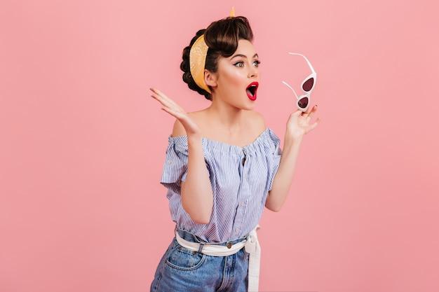 Geschokt pinup meisje met zonnebril. studio shot van emotionele vrouw in vintage outfit geïsoleerd op roze achtergrond. Gratis Foto