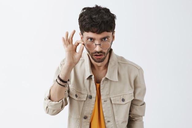 Geschokt stijlvolle bebaarde man poseren tegen de witte muur Gratis Foto