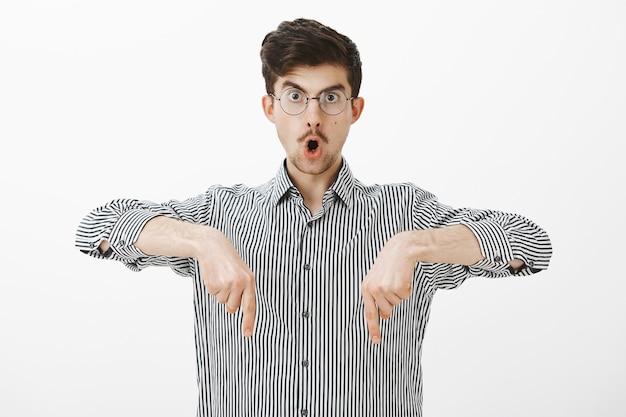 Geschokt verbaasd creatieve jonge kerel met snor in bril, naar beneden wijzend met wijsvingers, wauw zeggen en kaak laten vallen, iets geweldigs en verrassends naar beneden zien Gratis Foto